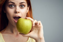 Young beautiful woman on a gray background holds an apple Stock Photo