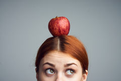 Young beautiful woman on a gray background holds an apple on her head, diet Stock Images