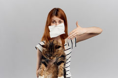 Young beautiful woman on a gray background holds a cat, an allergy to pets Stock Photography