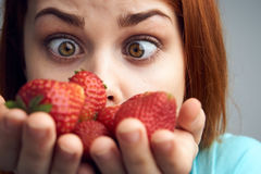 Young beautiful woman on a gray background holds a strawberry, berries Stock Image