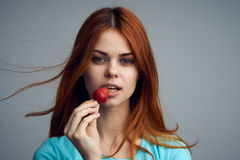 Young beautiful woman on a gray background holds a strawberry, berries Royalty Free Stock Images
