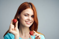 Young beautiful woman on a gray background holds a strawberry, berries Stock Photo