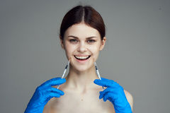 Young beautiful woman on a gray background in rubber gloves holds syringes, emotions, portrait, plastic surgery Stock Image