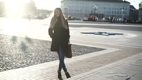 Young beautiful woman in gray coat with long hair, smiling and posing on camera fashion model in city center at sunset stock video footage