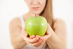 A young beautiful woman with a green apple Royalty Free Stock Photos