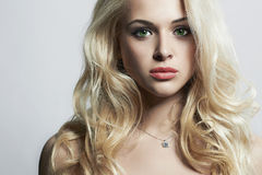 Young beautiful woman. Green eyes & Pink lips.  Blond girl. Curly hairstyle Stock Photography