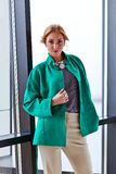 Young beautiful woman in green jacket Royalty Free Stock Image