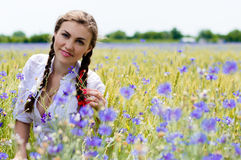Young beautiful woman in green wheet field on summer day outdoors Stock Photo