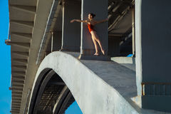 Young beautiful woman gymnast posing on bridge girder Royalty Free Stock Images