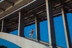 Young beautiful woman gymnast posing on bridge girder Stock Photos