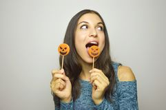 Young beautiful woman with halloween lollipops. Studio picture isolated on gray background. Royalty Free Stock Photos
