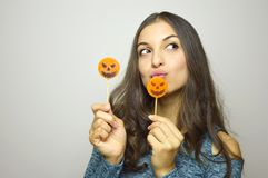 Young beautiful woman with halloween lollipops. Studio picture isolated on gray background. Young beautiful woman with halloween lollipops. Studio picture stock photography
