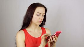 Young beautiful woman hand writing SMS, texting on smartphone. stock video