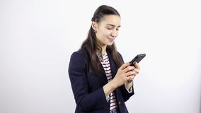 Young beautiful woman hand writing SMS, texting on smartphone. On a white Background stock video footage