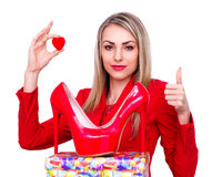 Young beautiful woman happy to receive red high heels shoes as a present and showing thumb up gesture Stock Photo