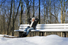 The young beautiful woman has a rest on a bench in the winter park Stock Images