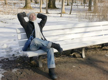 The young beautiful woman has a rest on a bench in the winter park Royalty Free Stock Images