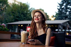 Young beautiful woman in a hat in a cafe on the terrace, smile, latte, summer Stock Photography