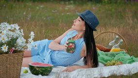 A young beautiful woman in a hat and dress is drinking lemonade from a can while sitting on a plaid on the green grass. Picnic basket, a bouquet of daisies stock video footage