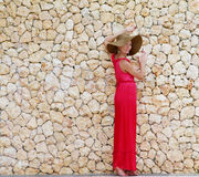 Young beautiful woman in hat next to stone wall Royalty Free Stock Images