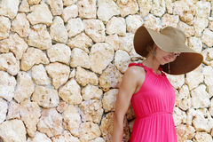 Young beautiful woman in hat next to stone wall Royalty Free Stock Photo