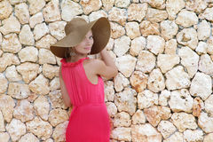 Young beautiful woman in hat next to stone wall Royalty Free Stock Photos
