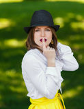Young beautiful woman in hat shows hush sign. Young beautiful sexy woman in stylish straw fedora hat showing hush sign with finger at her red lips, making Royalty Free Stock Photos