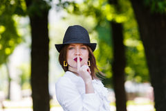 Young beautiful woman in hat shows hush sign. Young beautiful sexy woman in stylish straw fedora hat showing hush sign with finger at her red lips, making Stock Photography