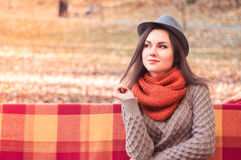 Young beautiful woman in a hat sitting on a bench in an autumn park Royalty Free Stock Photography