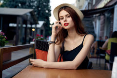 Young beautiful woman in a hat at a table in a cafe on a terrace in the summer calls on the phone Royalty Free Stock Images