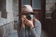 Young beautiful woman in hat is taking picture with old fashioned camera, outdoors stock photos