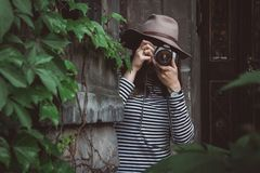 Young beautiful woman in hat is taking picture with old fashioned camera, outdoors stock images