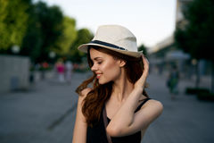 Young beautiful woman in a hat walking along a street in the city Stock Images
