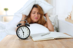 Young beautiful woman hates waking up early in the morning. Sleepy girl looking at alarm clock and trying to hide under the pillow Stock Images