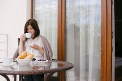 Young beautiful woman having breakfast on a cozy terrace Royalty Free Stock Image