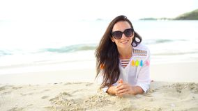 Young beautiful woman having fun on tropical seashore. Happy girl lying at white sand tropical beach. Young happy woman on white beach walking stock footage