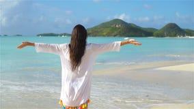 Young beautiful woman having fun on tropical seashore. Happy girl walking at white sand tropical beach. SLOW MOTION. Young happy woman on white beach walking stock video footage