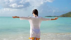 Young beautiful woman having fun on tropical seashore. Happy girl walking at white sand tropical beach. SLOW MOTION. Young happy woman on white beach walking stock video
