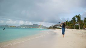 Young beautiful woman having fun on tropical seashore. Happy girl walking at white sand tropical beach before rain stock video