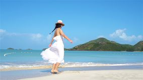Young beautiful woman on white sand tropical beach. Young beautiful woman having fun on white sand tropical beach. Caucasian girl with hat background the sea stock video footage