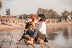 Woman having great time with her dog Basset Hound. Young beautiful woman having great time with her dog Basset Hound while sitting next to river stock photo