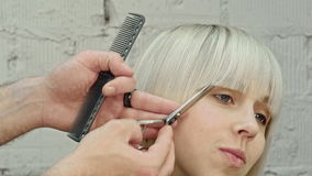 Young beautiful woman having her hair cut at the hairdresser's. stock video