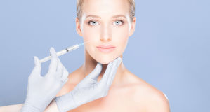 Young and beautiful woman having skin injections over blue background. Plastic surgery concept. stock images