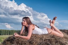 Young beautiful woman on hay Stock Photo