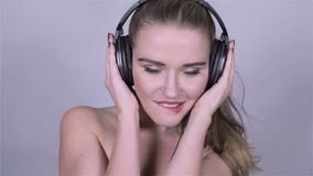 Young beautiful woman in headphones dancing in studio. stock footage