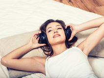 Young beautiful woman headphones listening music on bed Stock Photography