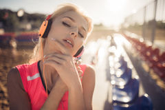 Young beautiful woman with headphones posing over beach volley seats Stock Images