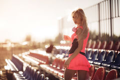 Young beautiful woman with headphones posing over beach volley seats. Back view. Stock Photos