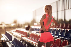 Young beautiful woman with headphones posing over beach volley seats. Back view. Stock Images