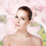 Young beautiful woman with healthy skin. Portrait of young beautiful woman with healthy skin. Roses background Stock Image